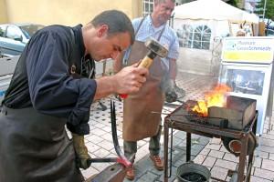 Martin Bäuml (vorne) beim Ausschmieden eines Stierkopfes. Im Hintergrund Ralf Häußler an der Esse.  Foto: Timo Deible